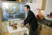 Hai chuyên gia của Accenture đang trình diễn công nghệ Virtual Dinner. Ảnh: AP.