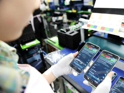 Một công nhân đang kiểm tra hai chiếc điện thoại Samsung Galaxy mới.