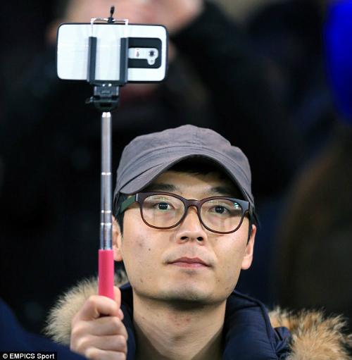 Một cổ động viên giơ gậy selfie trên sân vận động.