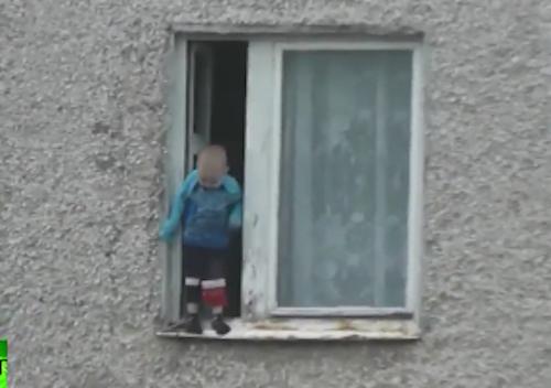 Em bé đứng cheo leo ở rìa cửa sổ tầng 8