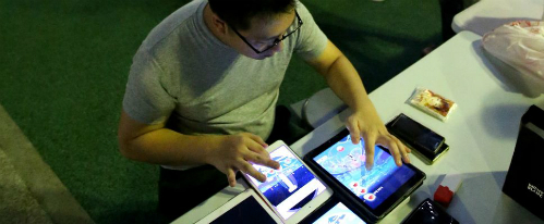 Tan đang tập trung làm việc trên máy tính bẳng với trò Pokemon Go.