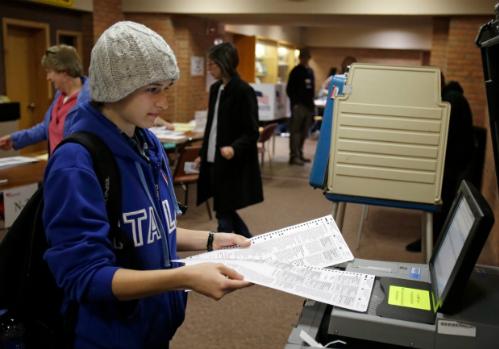 Một cử tri Ohio cho lá phiếu của mình vào máy quét trong cuộc bầu cử tổng thống năm 2012. Ảnh: AP