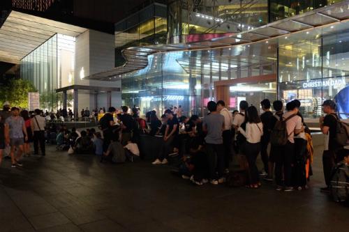 Tối xuống, hàng người xếp hàng trước cửa Apple Store Singapore vẫn kéo dài.