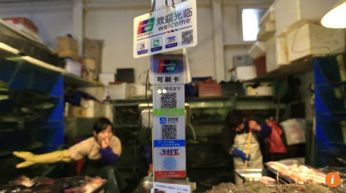 Gian hàng bán hải sản ở Bắc Kinh này chấp nhận các hình thức thanh toán không dùng tiền mặt khác nhau, bao gồm cả WeChat và Alipay. Ảnh: EPA