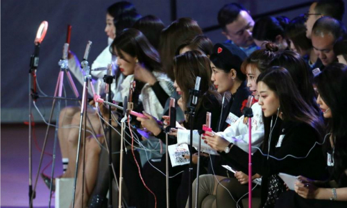 Khách mời sử dụng điện thoại di động để quay video trực tuyến trong một buổi trình diễn thời trang ở Bắc Kinh. Ảnh: EPA