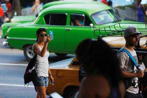 Một phụ nữ dùng điện thoại di động tại Cuba. Ảnh: Reuters.
