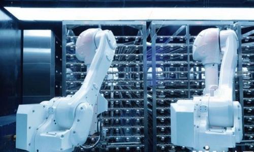 Cánh tay robot trong bếp sắp xếp các đĩa thực phẩm lên cho robot vận chuyển.