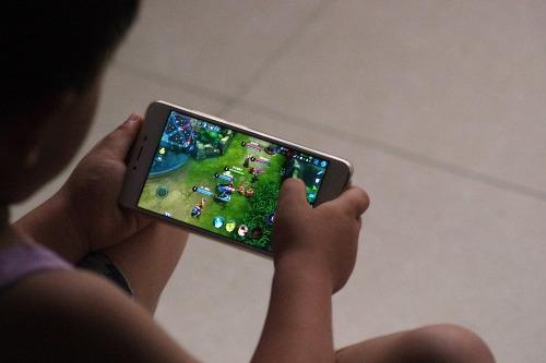 Trẻ em Trung Quốc đang chơi game Honor of Kings trên smartphone.
