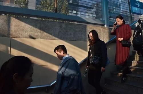 Người dân Trung Quốc đi bộ bên ngoài một trạm điện ngầm tại Bắc Kinh.