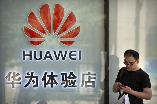 Một người đàn ông bên ngoài cửa hàng Huawei ở Bắc Kinh. Ảnh: AP.