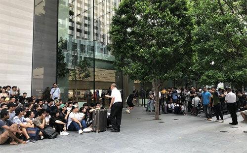 Đông đúc nhất thế giới chính là Apple Store tại Singapore, nơi có hàng trăm người đã bay từ Việt Nam sang từ ngày 19/9 để xếp hàng. 80-90% những người xếp hàng hôm nay là người Việt, một thương gia iPhone ở TP HCM cho biết. Mỹ Linh (thứ hai từ trái sang) có số thứ tự 001, tức sẽ trở thành người đầu tiên được mua iPhone tại Apple Store trên đường Orchard. Cô đi cùng nhóm bạn 5 người từ TP HCM và có mặt tại Singapore từ đêm qua.