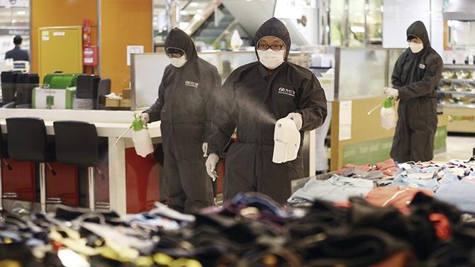 Công nhân mặc bộ đồ bảo hộ phun thuốc khử trùng để đề phòng Covid-19 tại một cửa hàng bách hóa ở Daegu. Ảnh: AP.