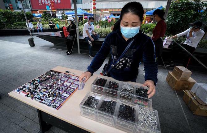 Chủ một cửa hàng linh kiện bày các sản phẩm mẫu trong quầy lưu động trên phố. Ảnh: Xinhua.